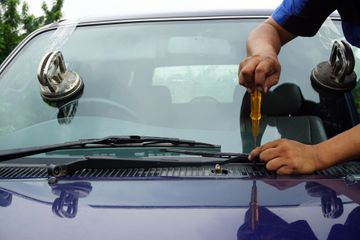 Technician repairing a car window using tools